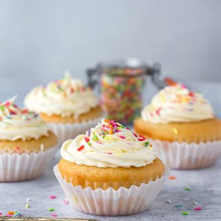 Side shot of a vegan vanilla cupcakes. Covered in vegan frosting and sprinkles.