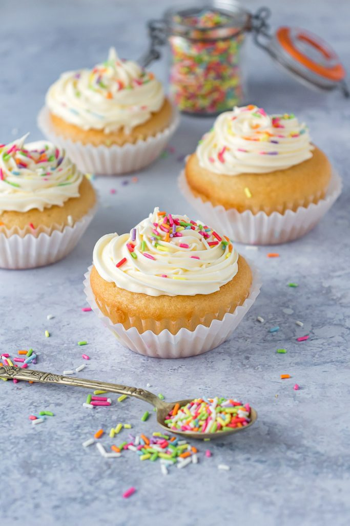 Four vegan cupcakes with frosting and sprinkles