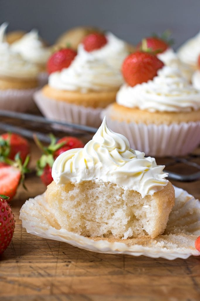 Vegan vanilla cupcake with a bite out, with vegan frosting and strawberries.