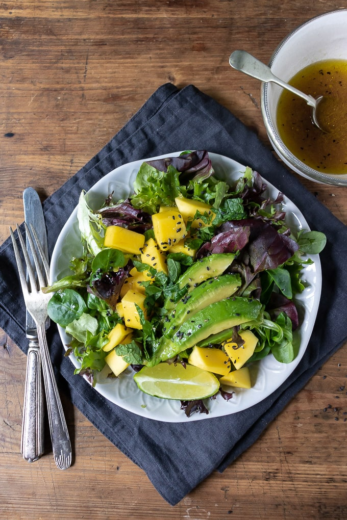 mango salad with lettuce and avocado and lime ginger dressing on a plate on a napkin