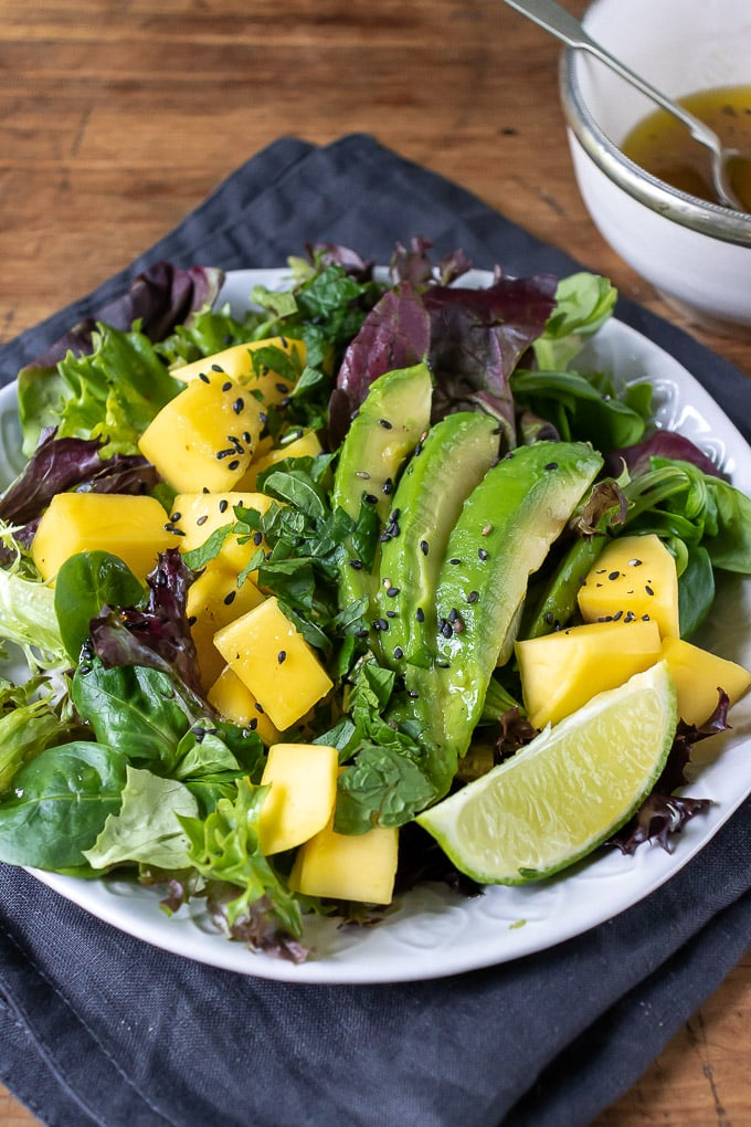 Close up of mango salad recipe, with lettuce, avocado, lime ginger dressing.