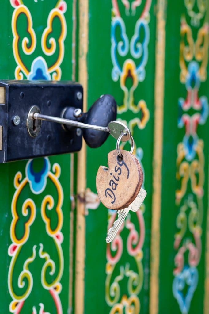 Close up of a wooden keychain with Daisy burned into it, in front of the green painted door of a yurt at Caalm Camp Dorset