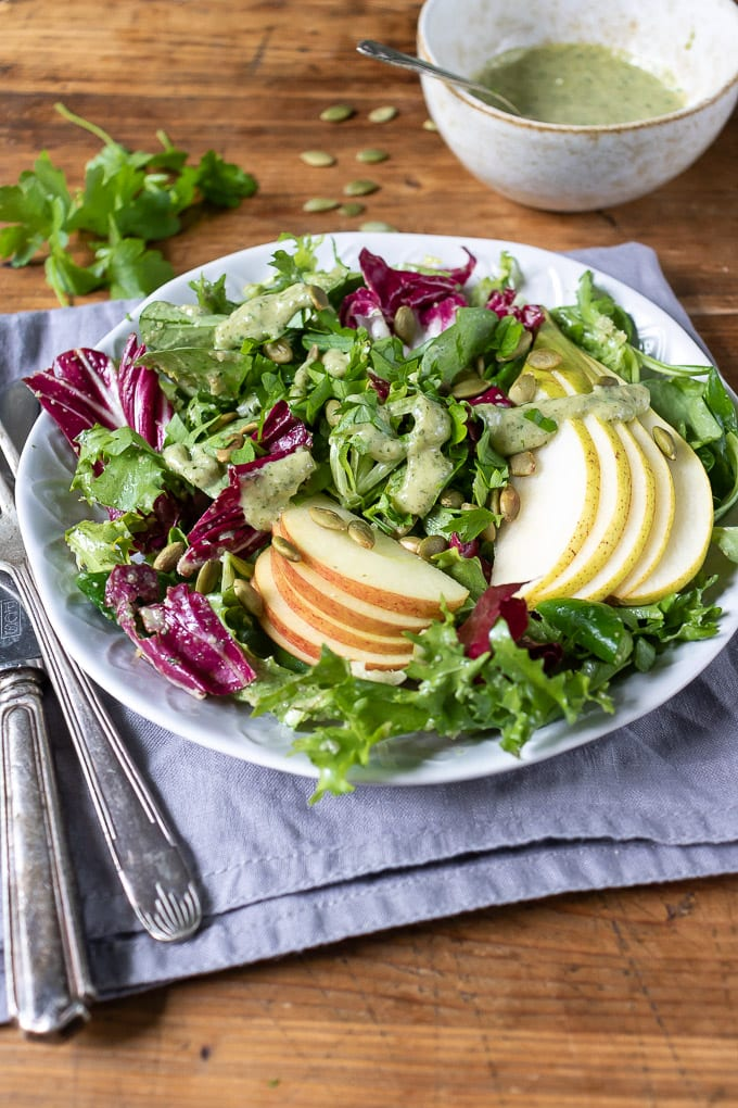 Overhead shot of a plate of green salad with slices of apple and pear