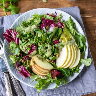 A plate of leafy green salad with radicchio, topped with apples, pears and pumpkin seed dressing