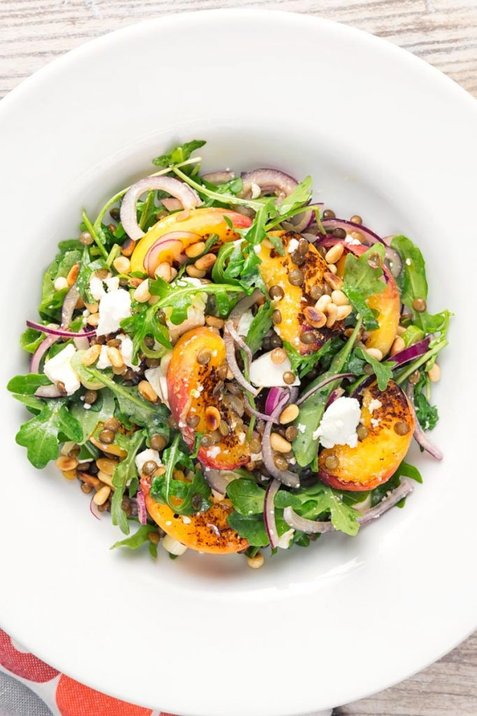 A bowl of peach feta cheese salad with lentils.