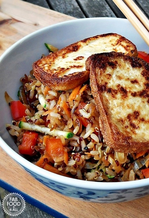 A bowl of warm rice and quinoa salad with fried tofu on top