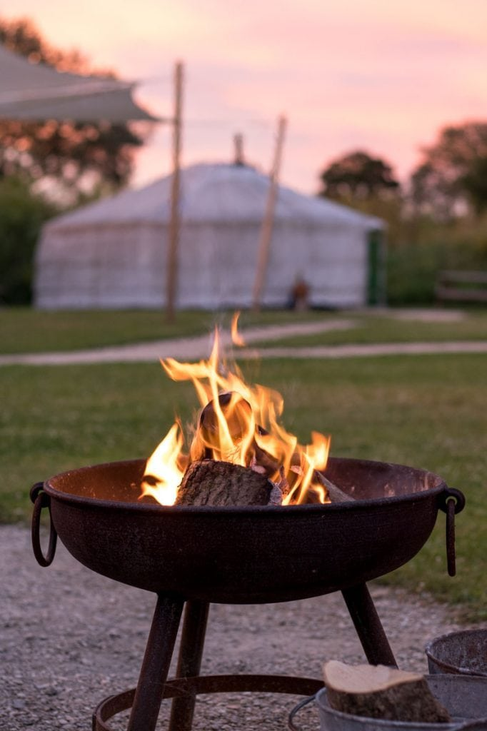 Fire pit ablaze with a yurt in the background and a pretty sunset sky