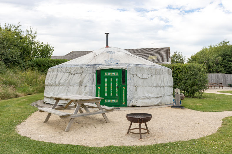 Yurt with picnic table and fire pit.