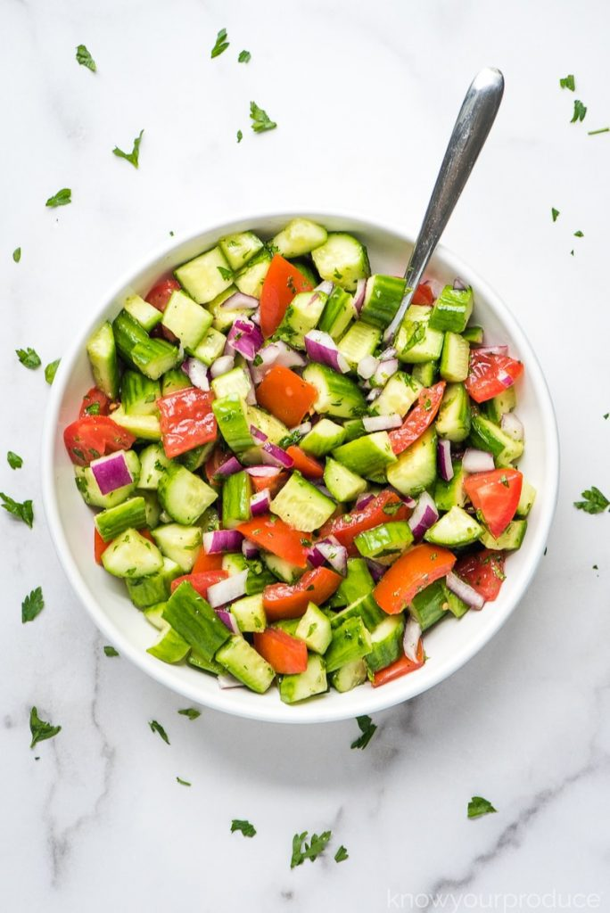 A large bowl of Shirazi salad with cucumbers, tomatoes and herbs