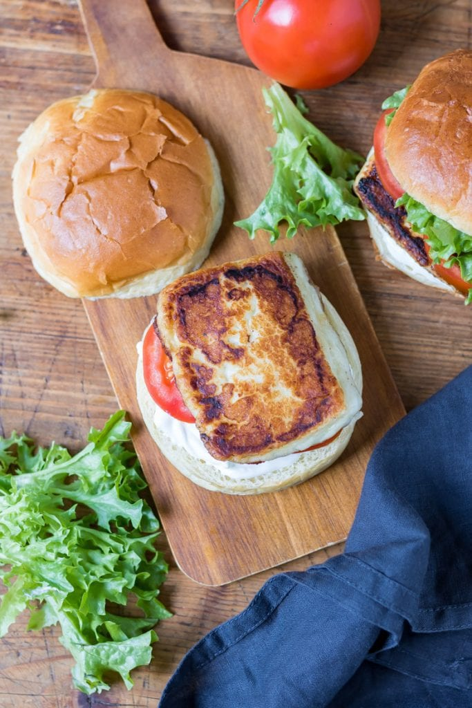 Halloumi burger on a wooden tray with cajun spices, brioche bun, lettuce and tomato. Shown with the top bun off.