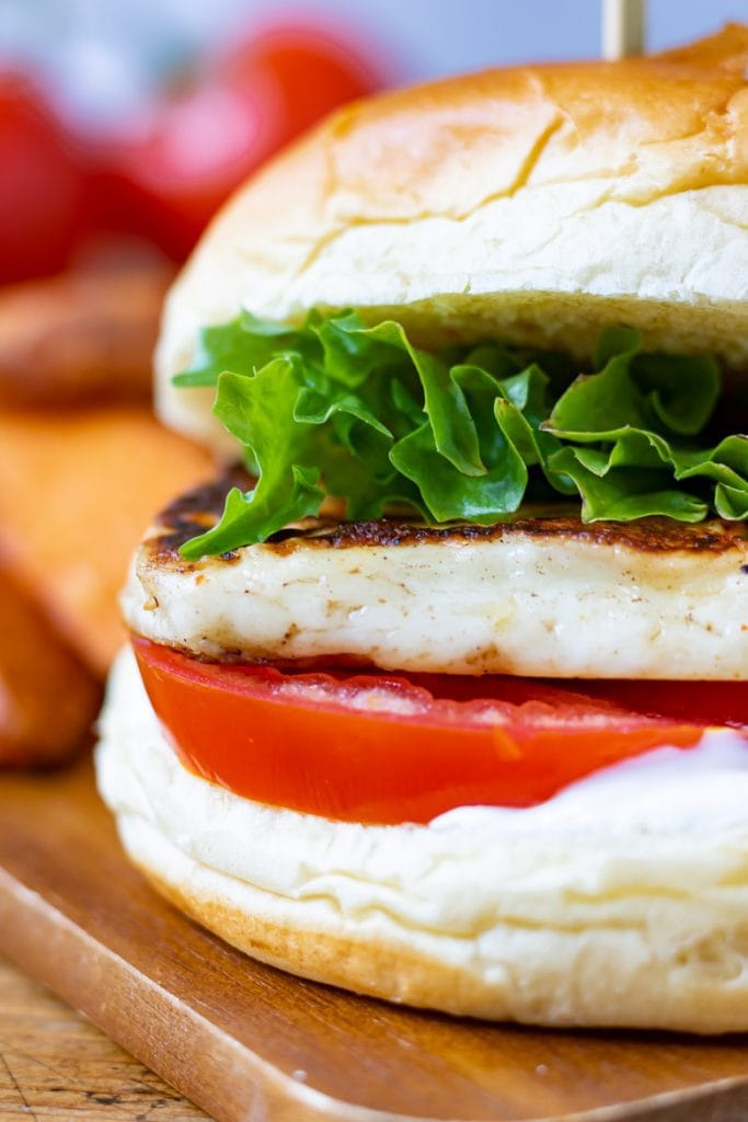 Close up of a grilled halloumi burger with tomato and lettuce.