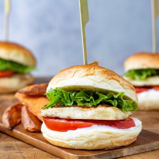 Side view of a cajun halloumi burger, with lettuce, tomato and brioche bun. With a skewer through it.