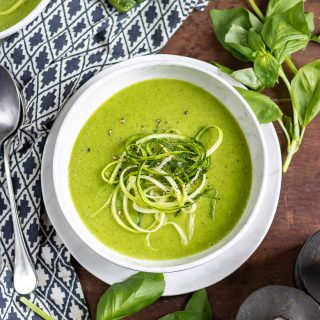 Overhead shot of a bowl of creamy zucchini soup with zoodles on top, surrounded by basil leaves
