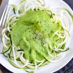 Overhead photo of a white plate of courgetti (spiralised courgette aka zucchini zoodles), with pea sauce on top.