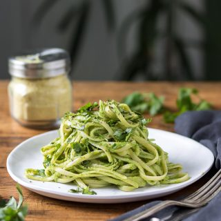 A plate piled with green spaghetti - pasta and a sauce made of avocado and herbs