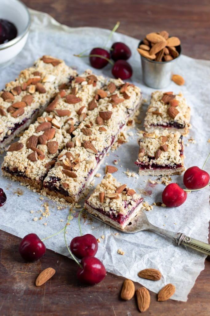 A batch of cherry bars recipe. Layers of almond oat base, cherry pie filling and crumble topping
