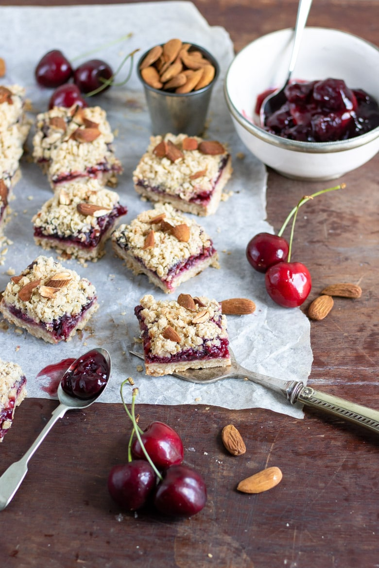 A wooden table with cherry bars, cherry pie filling and fresh cherries.