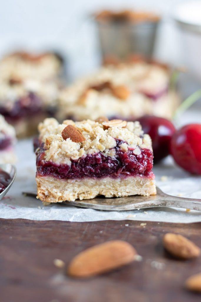 Close up of a cherry pie bar, with crumble topping.