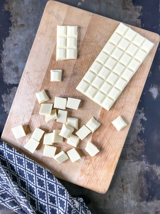 White chocolate cut up on a cutting board.