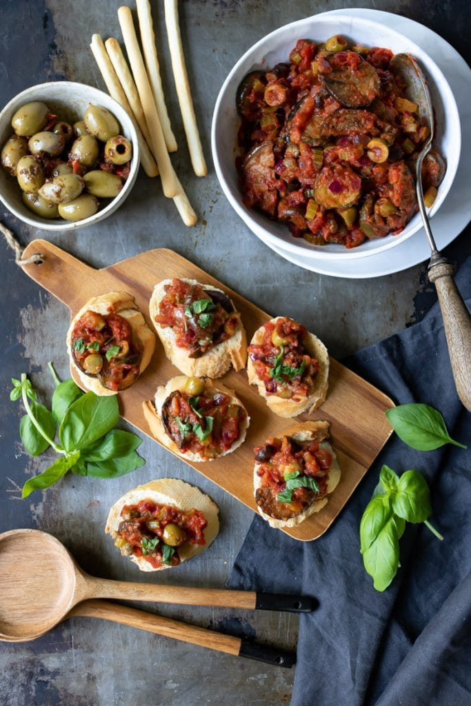 A table with a wooden tray of caponata crostini, a bowl of caponata Siciliana, breadsticks and olives.