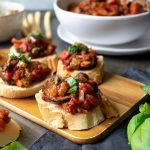 A wooden tray with Caponata alla Siciliana on rounds of toast served as an appetizer. With a bowl of the Italian eggplant stew in the background.