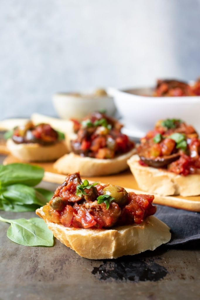 Side view of eggplant caponata siciliana recipe on slices of baguette, served as an appetizer.