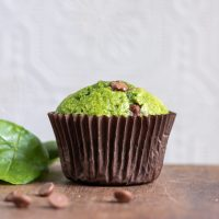 Side view of a sweet Spinach Muffin recipe with chocolate chips, with some chocolate in front