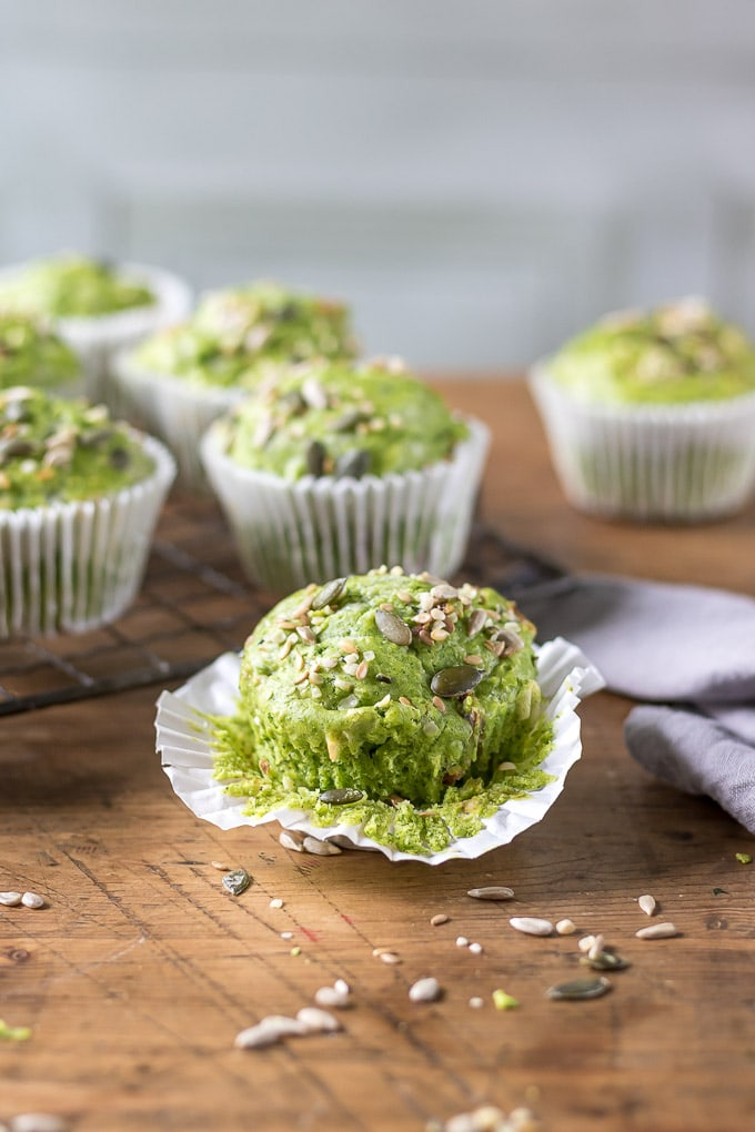 A green kale breakfast muffin with the paper case slightly removed and seeds scattered in front