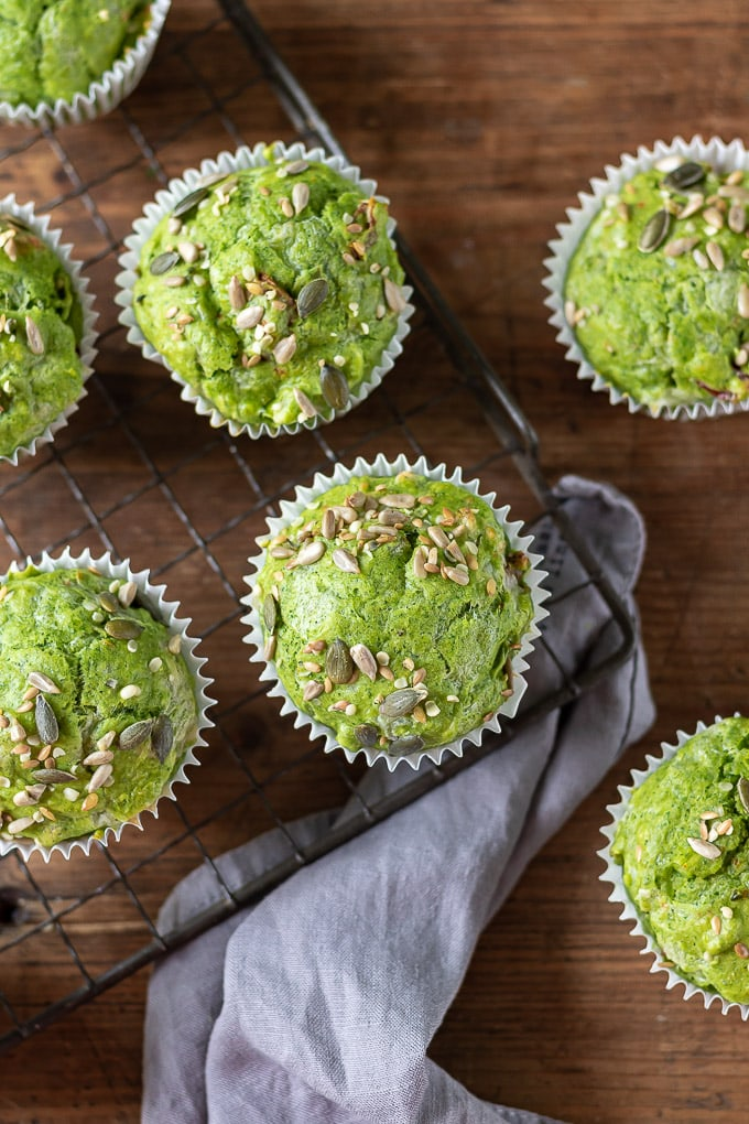 Overhead shot of kale green muffins on a cooling rack on wooden table.