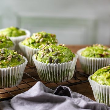 A wooden table with Kale Green Muffins recipe and grey napkin