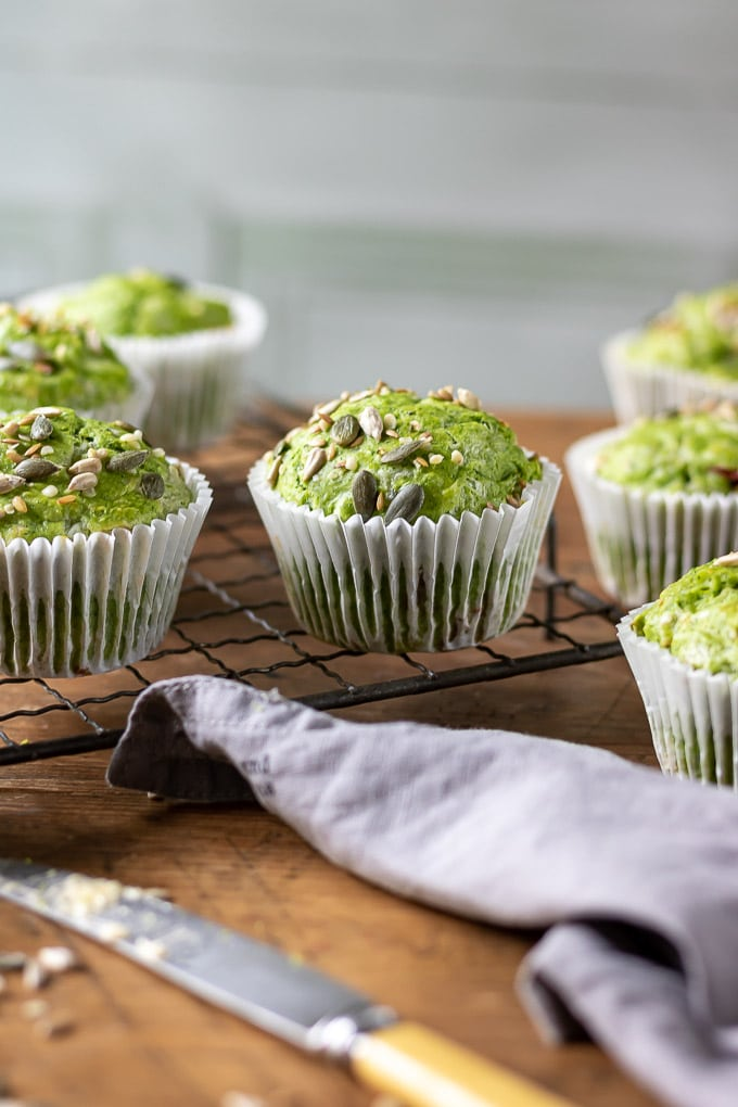 Bright green muffins (kale muffins with cheese and sun dried tomatoes) on a cooling rack on wooden table