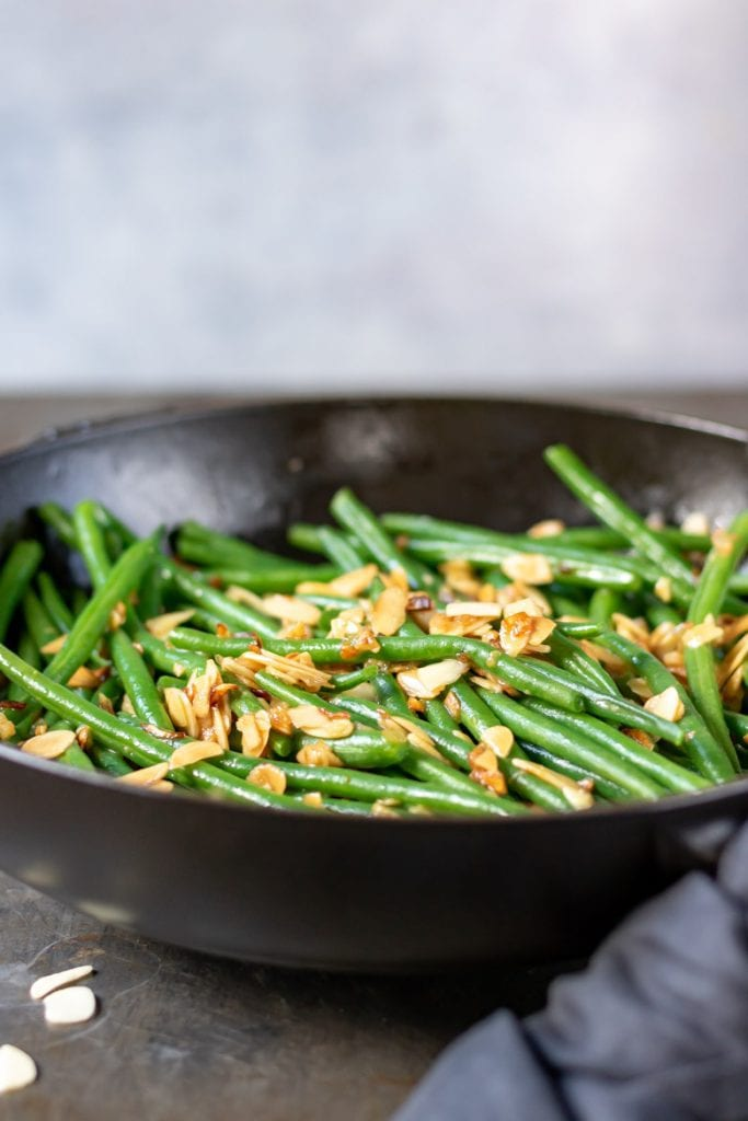 A cast iron skillet with green bean almondine recipe - string beans with toasted almonds