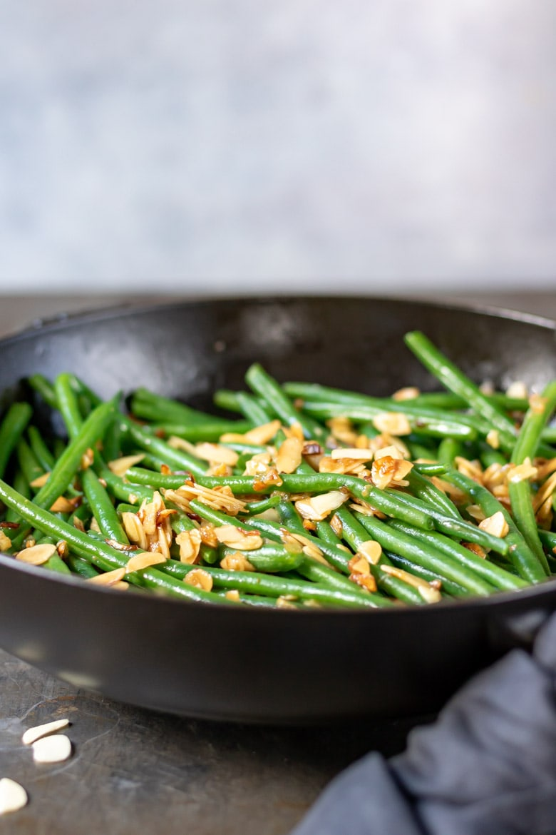 A cast iron skillet with green bean with almonds.