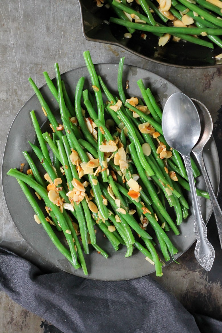 A vintage metal plate with green beans with almonds.