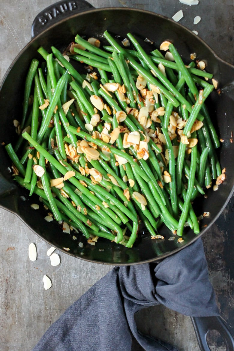 Overhead shot of a skillet with green beans almondine.