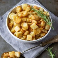 A bowl of parmentier potatoes (roasted diced potatoes recipe) on a grey napkin with sprigs of rosemary.