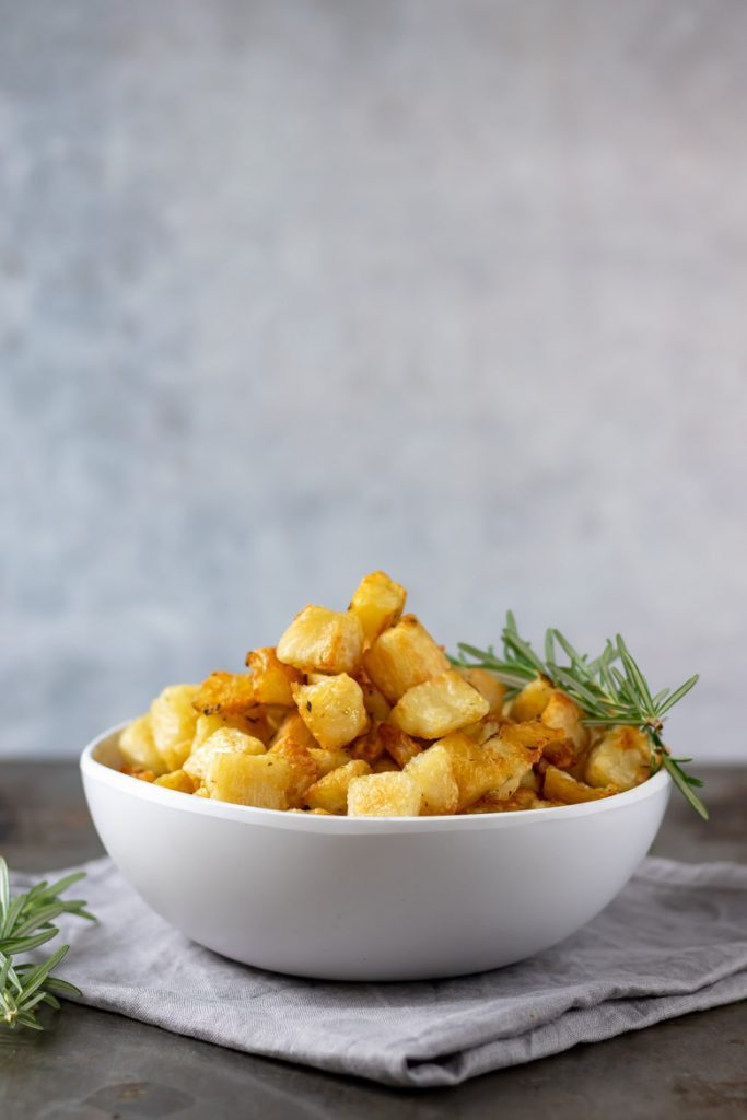 A white bowl filled with parmentier potatoes - small cubes of roasted potatoes with rosemary and garlic.