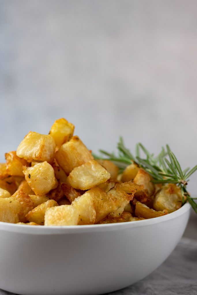 A bowl filled with cubed roasted potatoes - Parmentier Potatoes recipe. Vegan French side dish with garlic and rosemary.