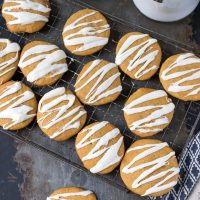 Overhead shot of soft iced pumpkin cookies with vanilla frosting drizzled on them. On a cooling rack.