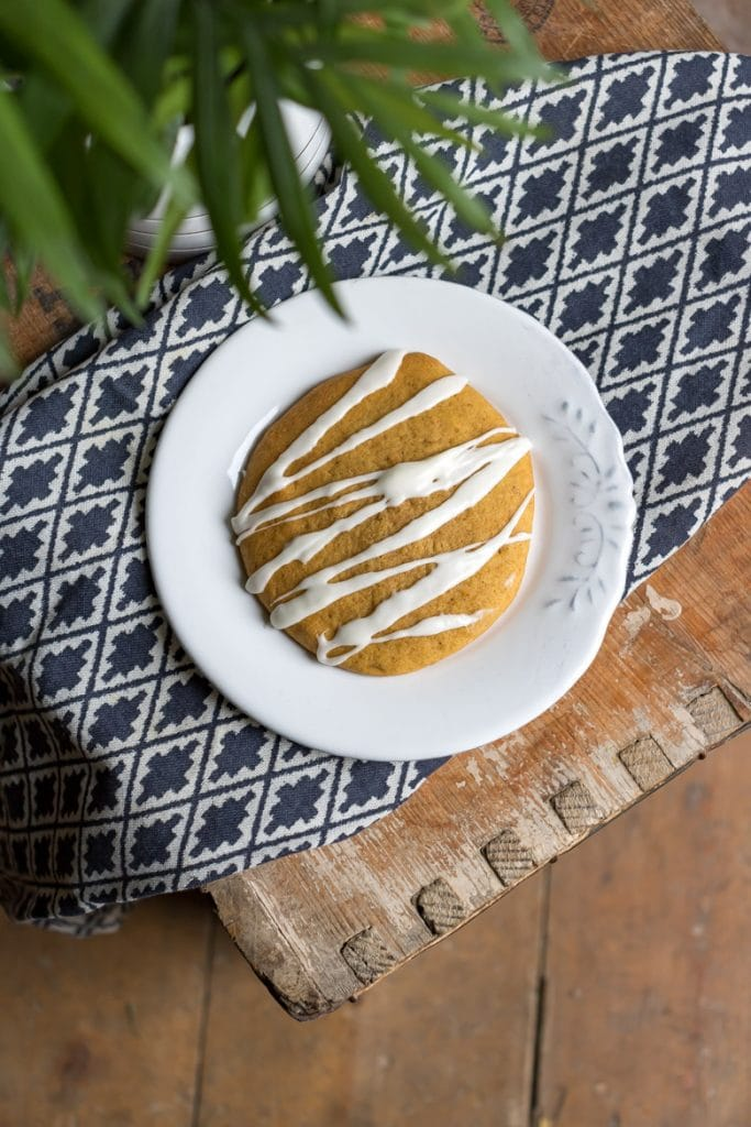 An iced pumpkin cookie on a white plate on a patterned napkin.