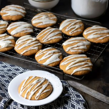 Iced pumpkin cookies on a cooling rack, with a soft pumpkin cookie in front on a plate. Get the recipe now.