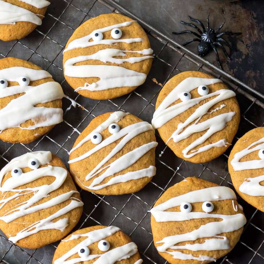 Pumpkin cookies drizzled with icing to look like Halloween mummys with candy eyes.