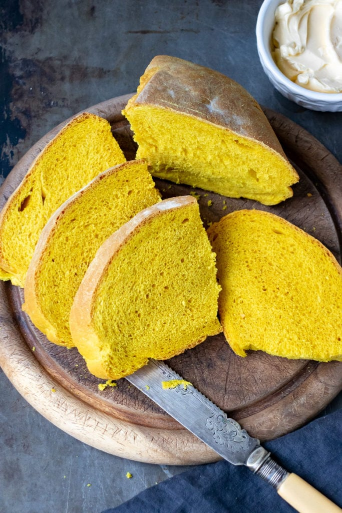 Slices of bright yellow Turmeric Bread on a vintage bread board with an antique knife.