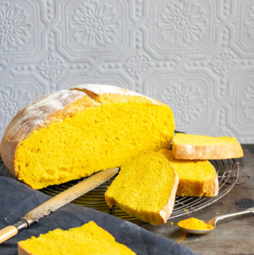 A loaf of Turmeric Bread recipe with slices cut next to it
