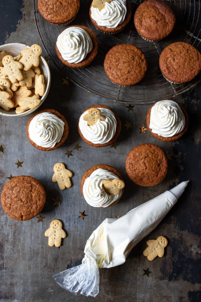 Overhead shot of pumpkin gingerbread cupcakes. Some have vanilla frosting and gingerbread men on them.