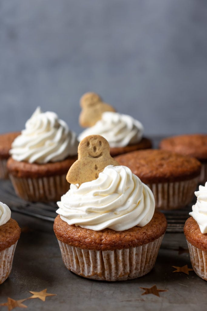 A pumpkin gingerbread cupcake with vanilla frosting and a mini gingerbread man on top.