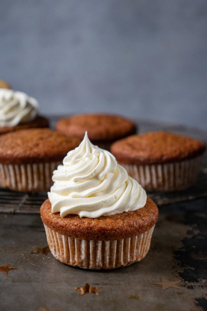Close up of a gingerbread pumpkin cupcake with vanilla frosting.