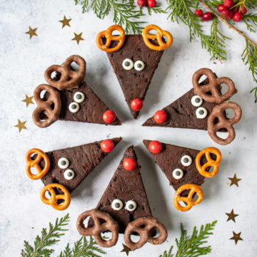 Reindeer brownies in a circle with red noses in the middle. Decorated for christmas with candy eyes and pretzel antlers.