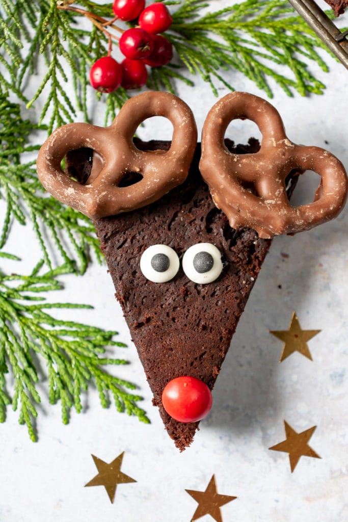 Close up of an avocado Reindeer Brownie recipe, with candy eyes, red candy nose and chocolate covered pretzel antlers.