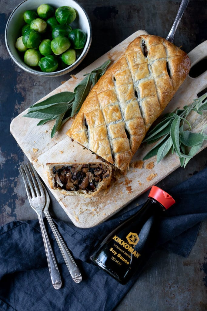A mushroom wellington on a cutting board next to sage leaves and sprouts.